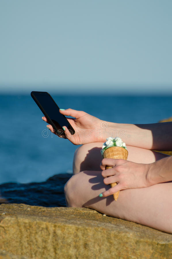 A girl sits on a rock near the sea with a smartphone and ice cream royalty free stock photography