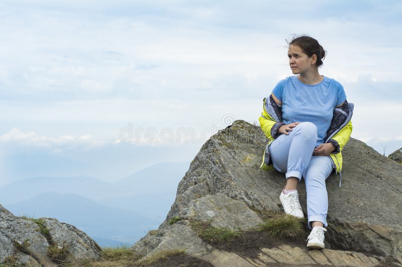 Girl sits on a rock over a cliff in the Carpathians royalty free stock images