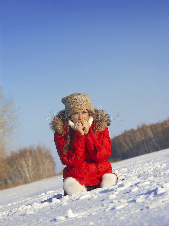 Girl sits on snow. The young girl in a winter jacket sits on snow stock photos