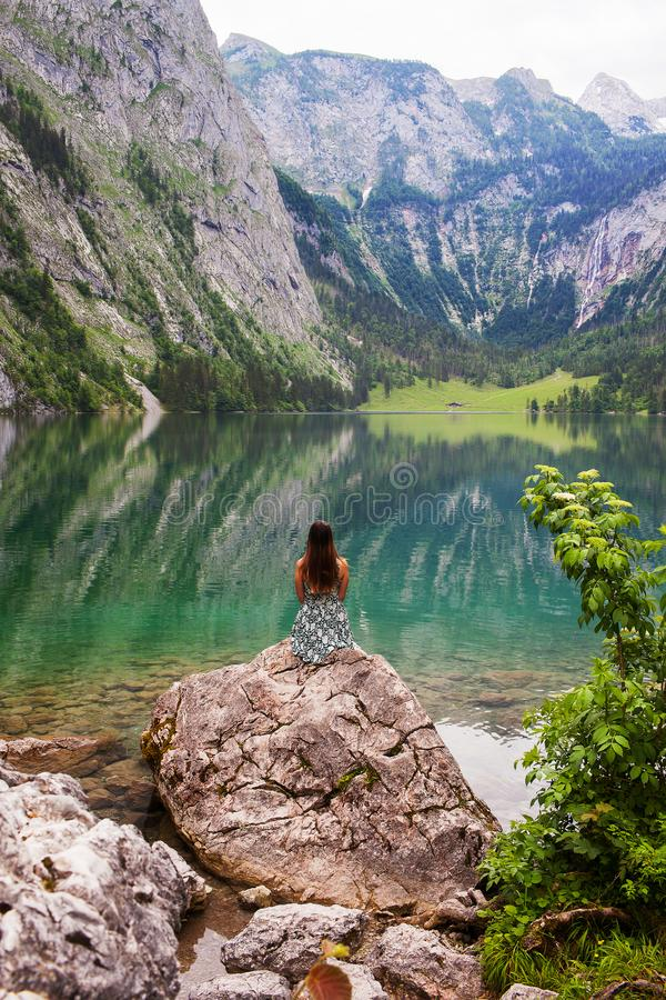 A girl sits on a stone on a large lake Obersee in the Alps royalty free stock photo