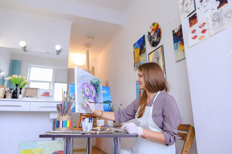Girl Sits on Stool at Easel And Writing Painting, Uses Brush to royalty free stock photography