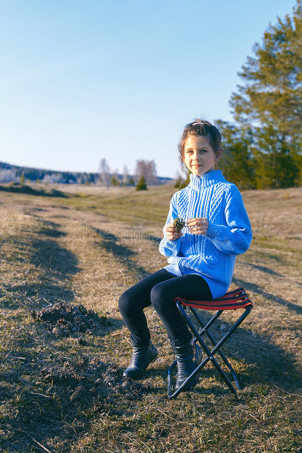 Girl sits on stool the meadow stock image