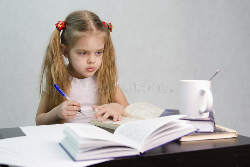 Girl leafing through the book and wrote on a sheet of paper abstract sitting at the table. A girl sits at a table and flips through the book and writes out the royalty free stock image