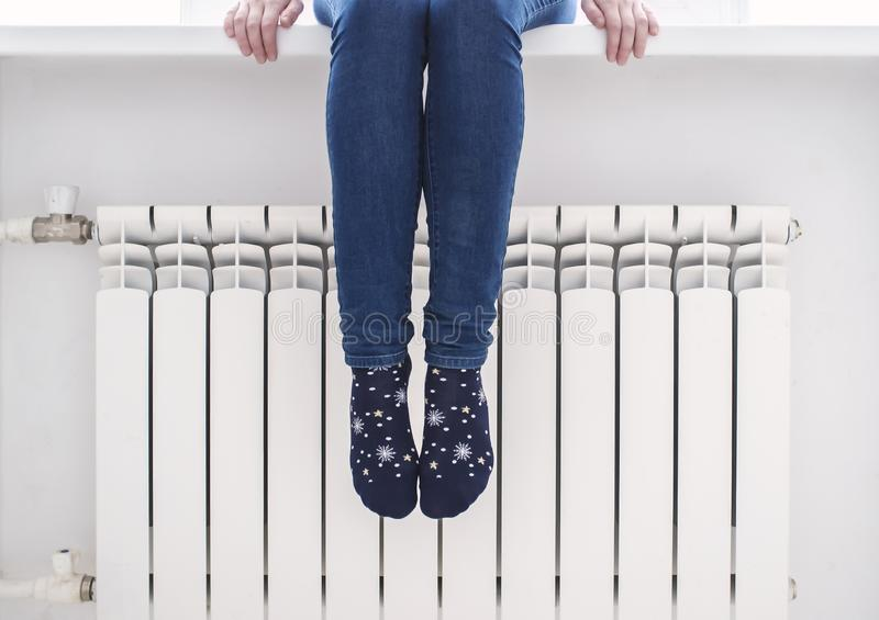 A girl sits on a window sill and warms the feet of the radiator, on a cold winter day. The girl sits on the windowsill and warms her feet in pretty socks at the royalty free stock photos