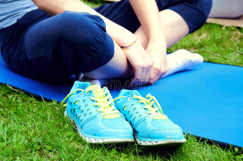 Girl sitthing on a yoga mat crosslegged with her blue sneakers o. N the grass royalty free stock images