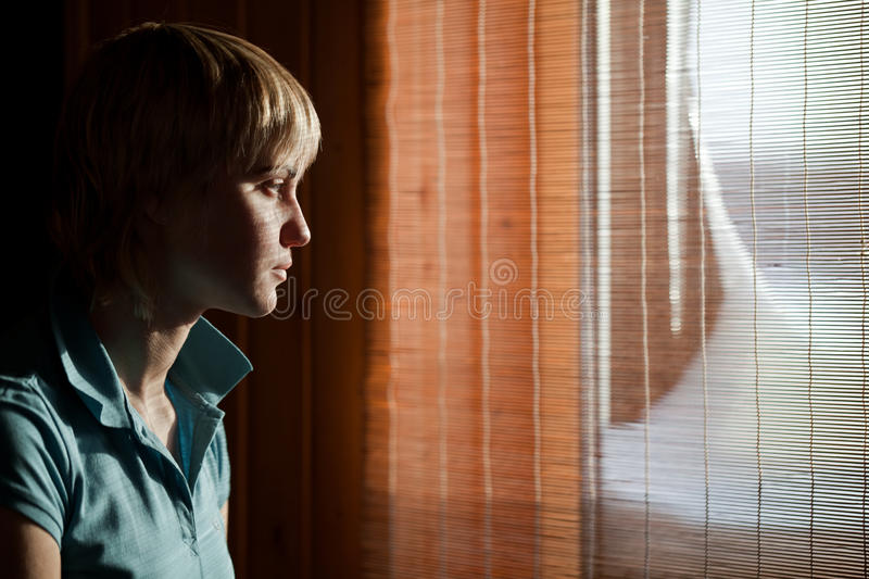 Girl sitting against a window stock photo