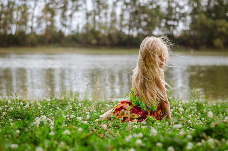 Little girl with long hair sitting in the grass by the river royalty free stock photography