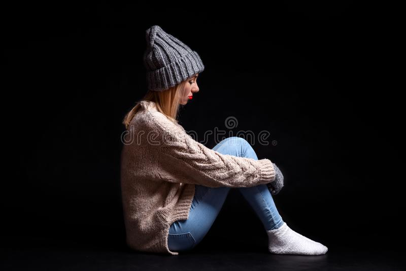 The girl is sitting alone on the floor on a black background of emptiness, hugging her legs with her hands and looking down, royalty free stock image