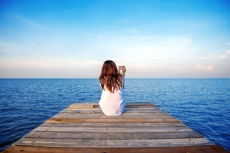 Girl sitting alone and hand holding camera on a the wooden bridge. Girl sitting alone and hand holding camera on a the wooden bridge on the sea stock photo