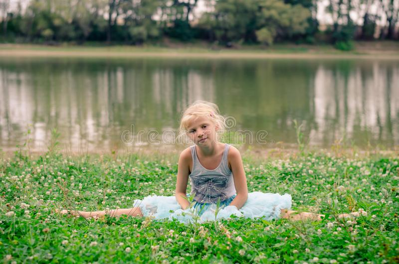 Little girl sitting in the grass by the river royalty free stock images