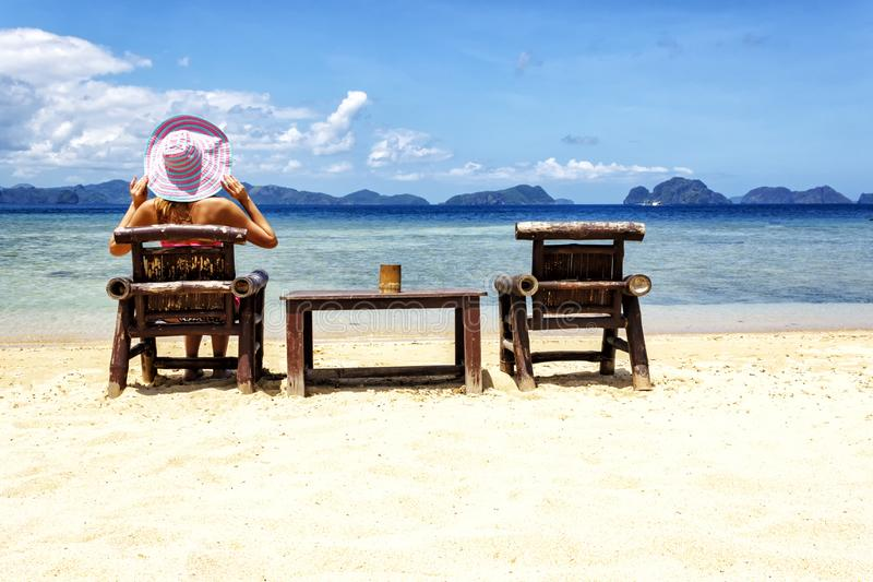 A girl sitting on a bamboo chair on the beach on a blue sea and sky background. place for text royalty free stock photo