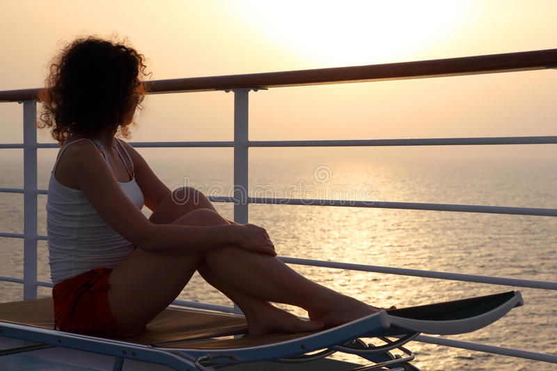 Girl sitting on beach chair at ship deck. And looking into the distance side view full body stock photography