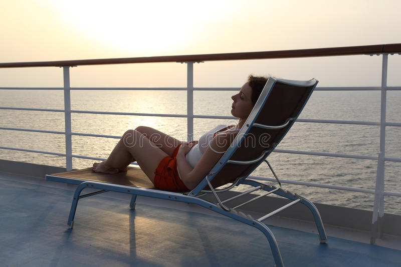 Girl sitting on beach chair at ship deck. Side view full body stock photos