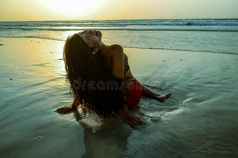 The girl is sitting on the beach royalty free stock photos