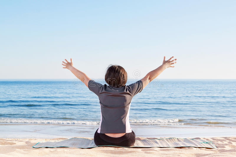 Download The Girl Is Sitting On The Beach And Welcomes Peace. Stock Image - Image: 31968443