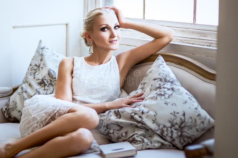 Girl sitting on a bed in a white dress a nice white background stock photography