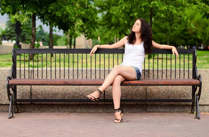 Latin teenie posing topless on park bench