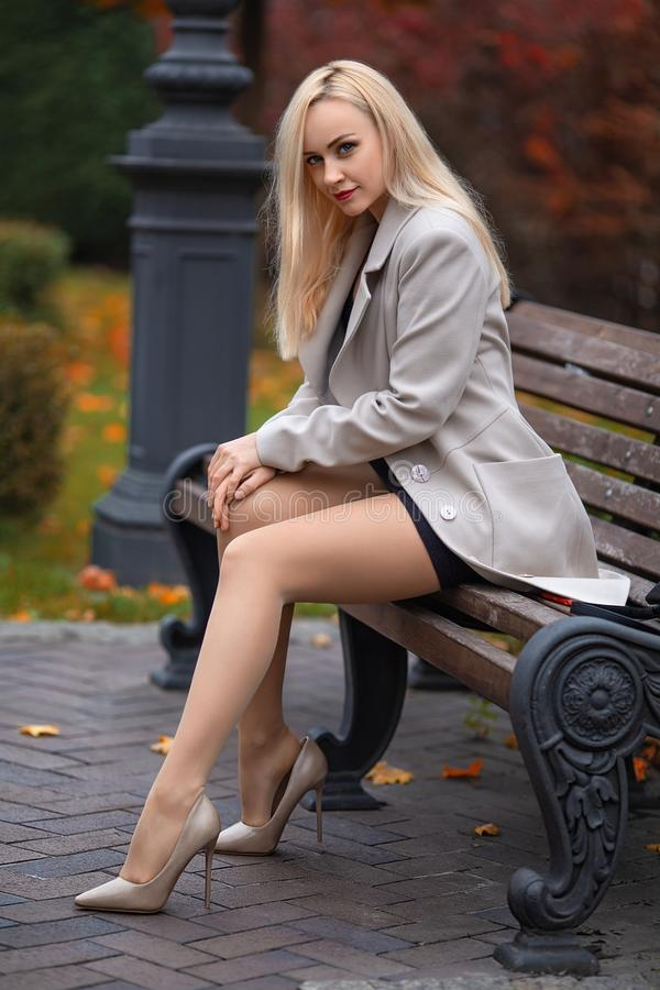 Girl sitting on the bench in the autumn park. Beautiful girl in the coat with perfect legs sitting on the bench in the autumn park stock photos