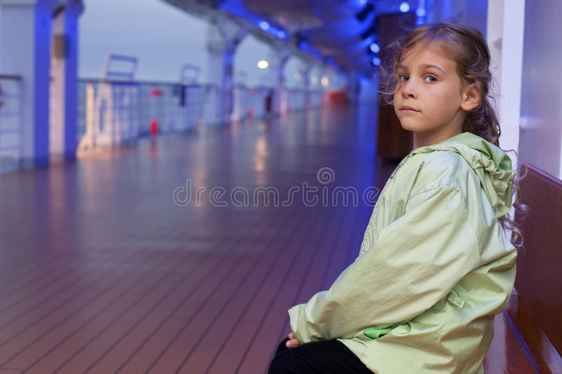 Girl sitting on bench on deck of ship