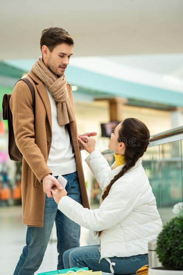 Girl sitting on bench and holding hands with standing man in. Shopping mall stock photography