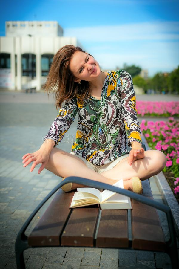 A girl is sitting on a bench in a lotus pose. royalty free stock photo