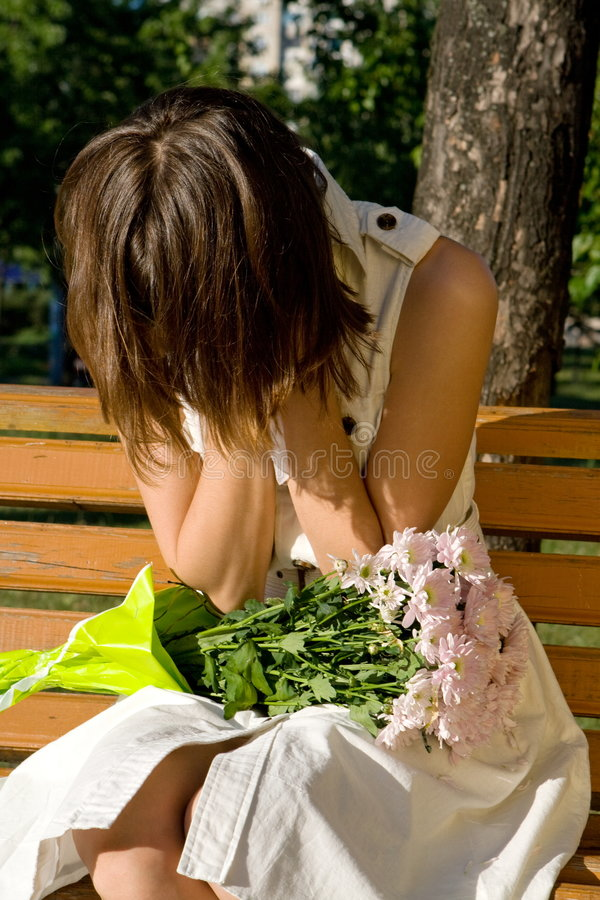Girl sitting on a bench in a park crying stock image