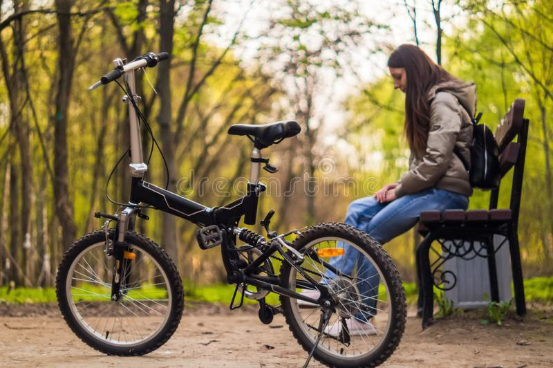 The girl is sitting on the bench and there is a bicycle in front of her stock images