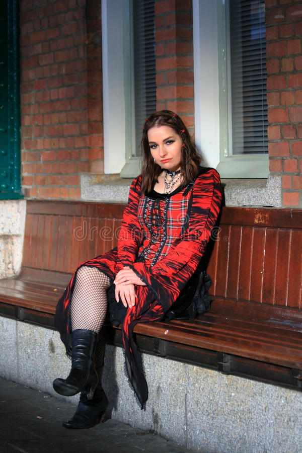 Girl sitting on bench wearing red dress stock photo