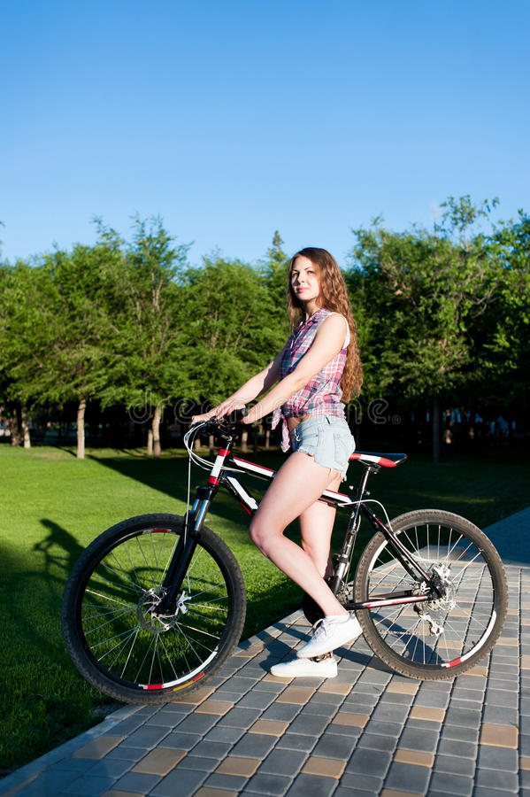 Girl sitting on bicycle stock photo. Image of grass ...