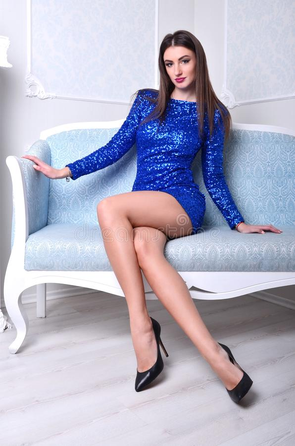 Girl sitting on the blue couch royalty free stock photo