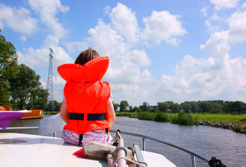 Girl sitting on a boat. Girl (4Yr) with life jacket sitting on a boat stock images