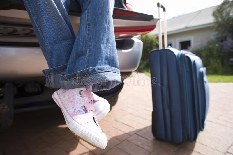 Girl (10-12) sitting in boot of car by suitcase, low section stock image