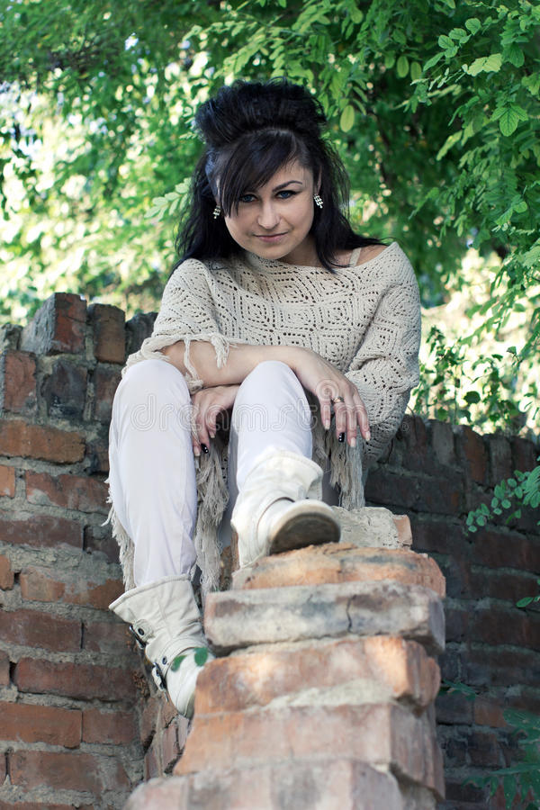Girl sitting on a brick wall stock photos