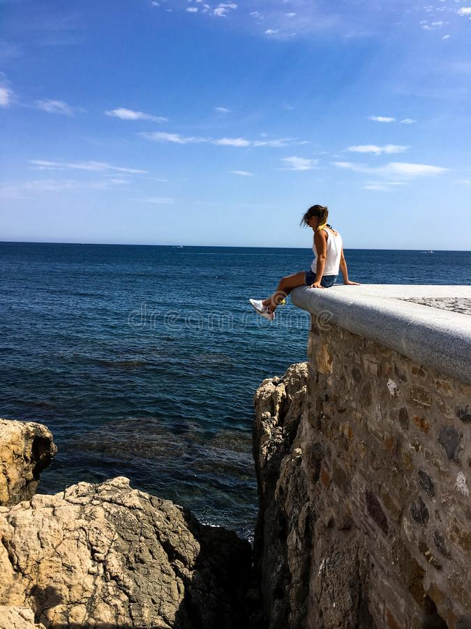 Girl sitting on castle pier above water royalty free stock photos
