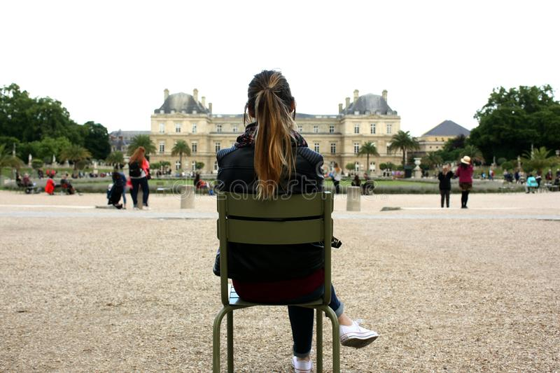 Girl sitting on a chair looking at a public building back shot. Outdoor, woman, old, city, young, exterior, day, rear, town, tourism, enjoy, history, house royalty free stock images