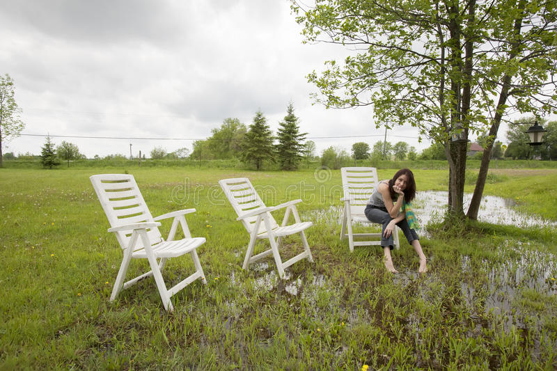 Girl Sitting on Chair in Rain Soaked Yard stock image