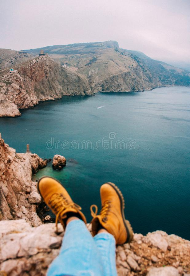 Girl sitting on cliff in front of breakage above sea stock images