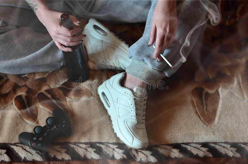 A girl sitting on the couch, smoking a cigarette, drinking beer. And playing on a game console in a smoky interior. The concept of wrong unhealthy lifestyles stock photography