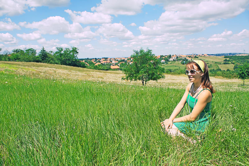 Girl sitting in country field stock image