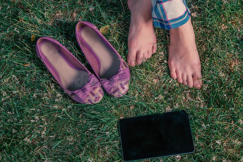Girl sitting crosslegged on grass with her shoes and tablet computer near, top view. Barefoot harmony, girl sitting crosslegged on grass with her shoes and royalty free stock image
