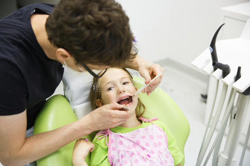 Girl sitting on dental chair on her regular dental checkup. Child patient sitting on dental chair in paediatric dentists office on her regular checkup for caries stock image