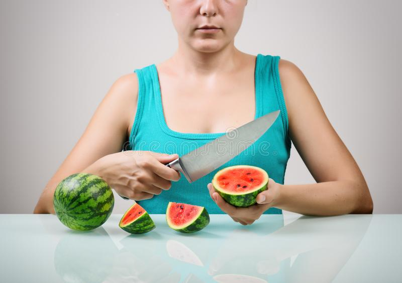 Girl using big knife for cutting juicy red small watermelons stock photography