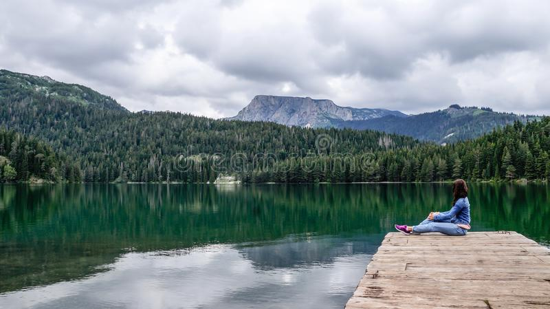 Girl sitting on the dock of the black lake in the Durmitor national Park. Montenegro. royalty free stock image