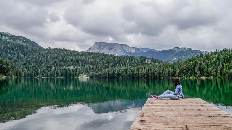 Girl sitting on the dock of the black lake in the Durmitor national Park. Montenegro. stock photography
