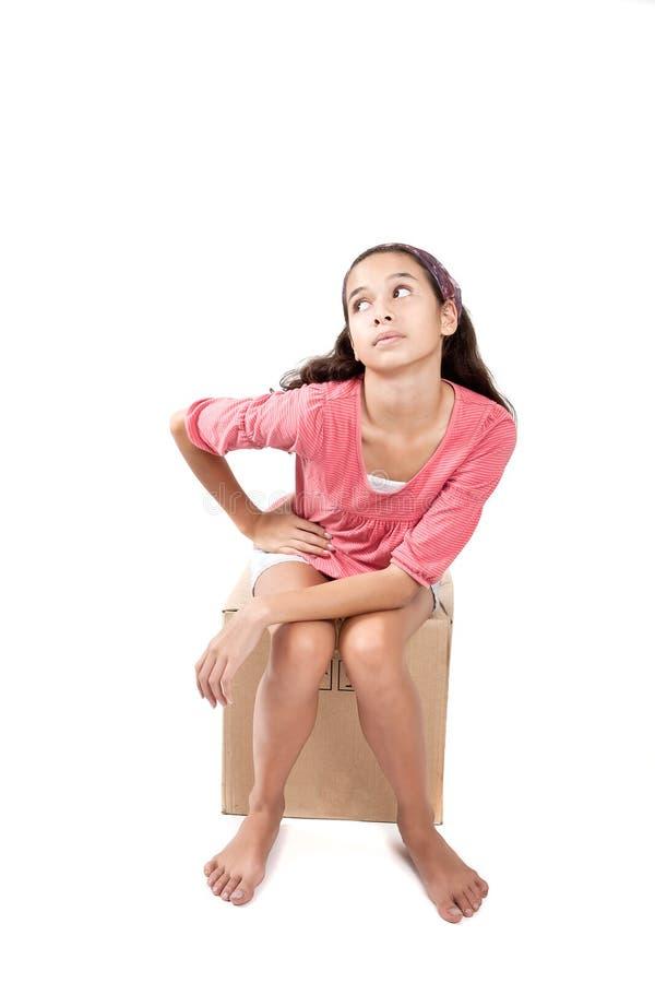 Girl sitting on empty cardbox box stock photography