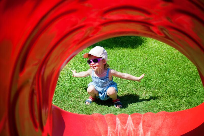 Girl sitting in the end of a red plastic slides royalty free stock photos
