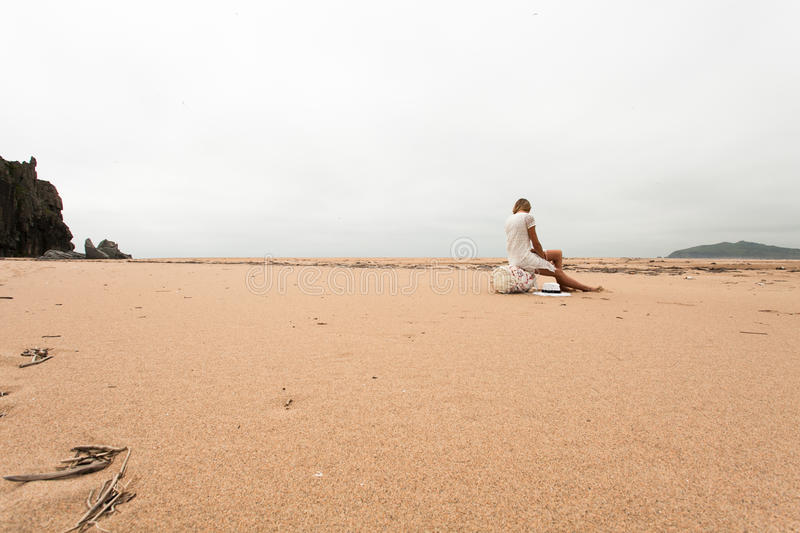 Girl sitting on a fishing buoy on the sandy coast of the sea. stock photography