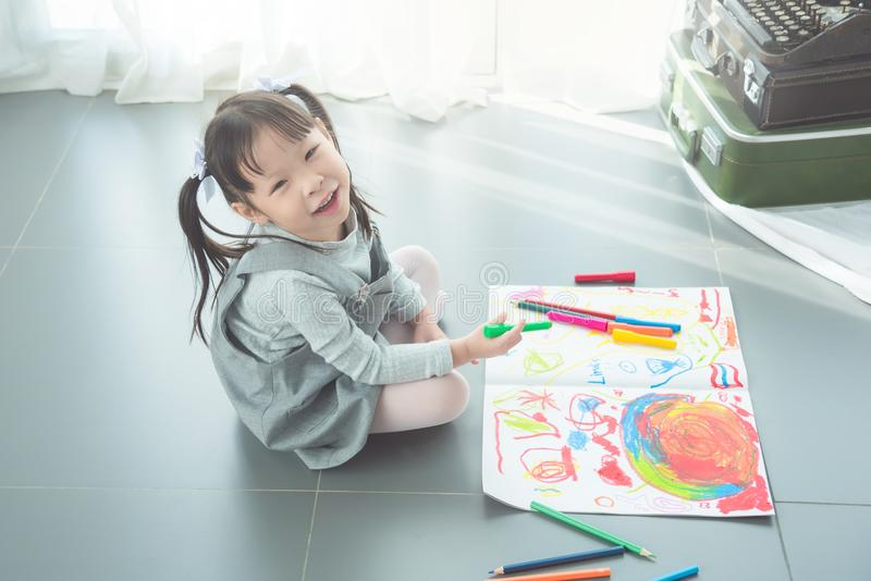 Girl sitting on the floor and drawing picture by crayon stock photography