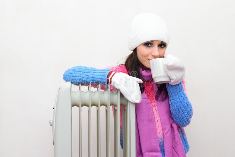 Girl sitting on the floor next to a radiator and drinking tea stock image