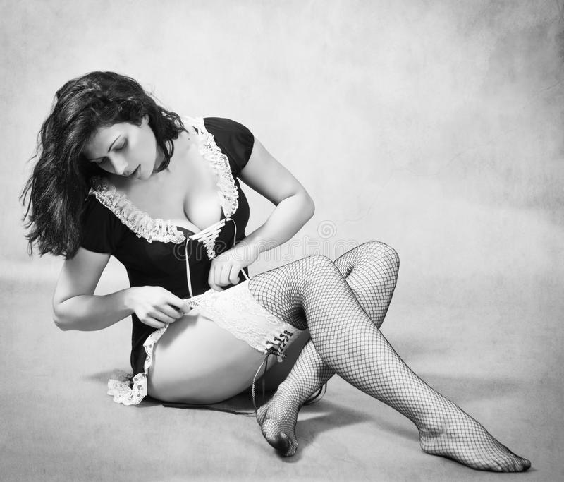 Girl sitting on the floor, putting on stockings stock photo